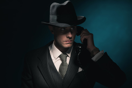 bel homme: Vintage young detective on the phone with hat in suit and tie. Dark blue background.