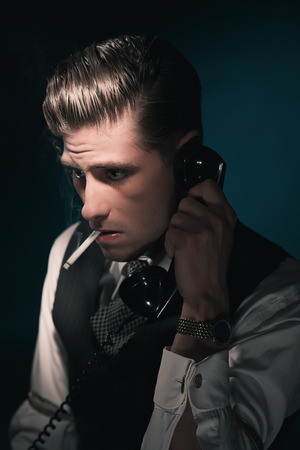 combed: Vintage stylish detective in waistcoat and tie calling and smoking cigarette. Hair combed back. Against dark blue wall. Stock Photo