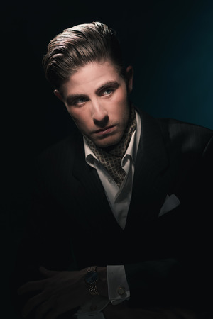 dandy: Stylish Vintage fashion dandy young man with scarf in suit. Against dark blue wall. Stock Photo