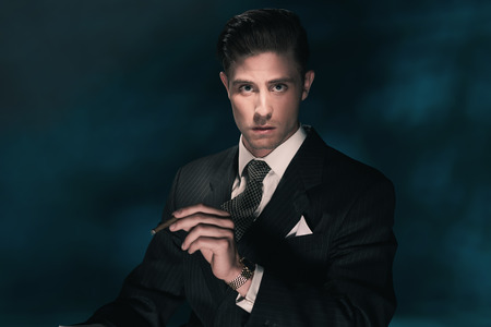 combed: Cigar smoking vintage businessman in suit and tie. Hair combed back. Against dark blue background. Stock Photo