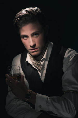 combed: Retro fashion young man with glass of whiskey in waistcoat. Greasy Hair combed back. Dark blue background.
