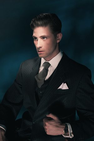 combed: Vintage fashion dandy man in suit and tie sitting on chair. Hair combed back. Dark blue background. Studio shot.
