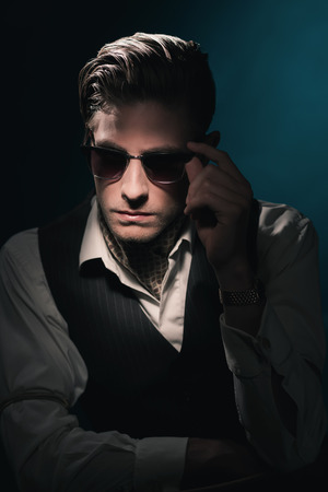 combed: Handsome retro fashion man with vintage shades in waistcoat and scarf. Slick hair combed back. Against Dark blue background. Stock Photo