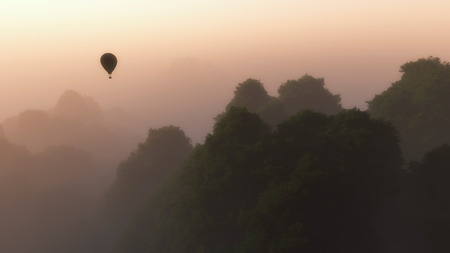 mist: Hot air balloon floating through hazy mountains covered with trees in the mist.