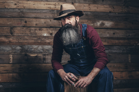 dungarees: Vintage worker man with long gray beard in jeans dungarees holding whiskey. Sitting on wooden crate in barn. Stock Photo