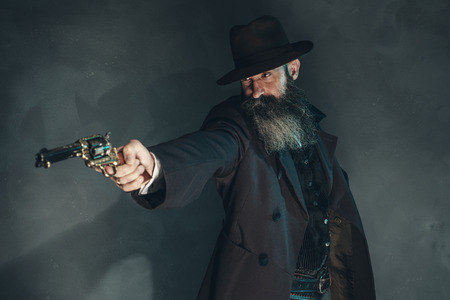 cowboy beard: Gun shooting vintage crook with long beard in 1900 style clothing against grey wall.
