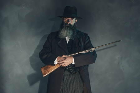 vintage rifle: Spooky vintage beard man with rifle in 1900 style fashion against grey wall.