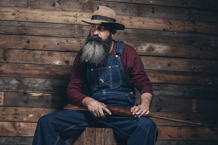 vintage rifle: Vintage farmer holding rifle sitting on wooden crate in barn.