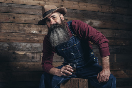 Vintage worker man with long gray beard in jeans dungarees holding whiskey. Sitting on wooden crate in barn. Stock Photo