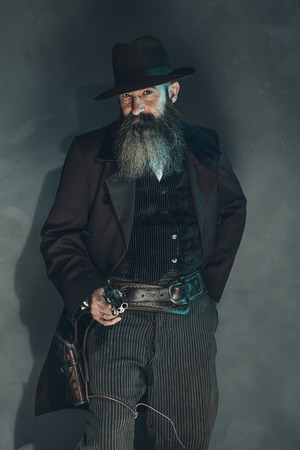 crook: Gun shooting vintage crook with long beard in 1900 style clothing against grey wall.