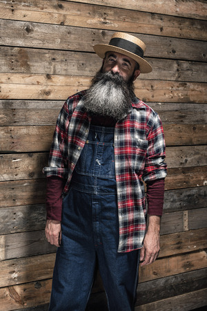 gray beard: Vintage worker man with long gray beard in jeans dungarees. Standing in front of wooden wall.