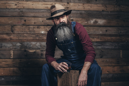 Vintage worker man with long gray beard in jeans dungarees holding whiskey. Sitting on wooden crate in barn. Standard-Bild