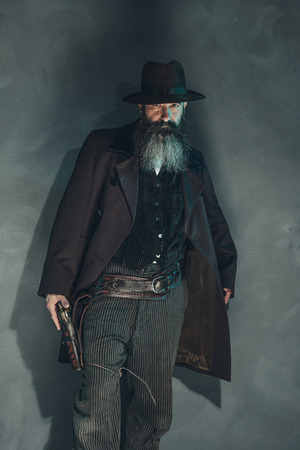 crook: Vintage crook with long beard holding gun in 1900 style clothing against grey wall.