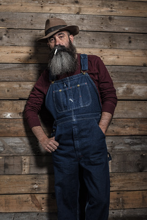 dungarees: Smoking vintage worker man with long gray beard in jeans dungarees. Standing against wooden wall.