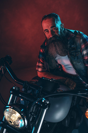 gray beard: Cool man with long gray beard on motorcycle at night.