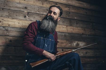 granjero: Agricultor titular rifle vendimia de pie contra la pared de madera en el granero. Foto de archivo