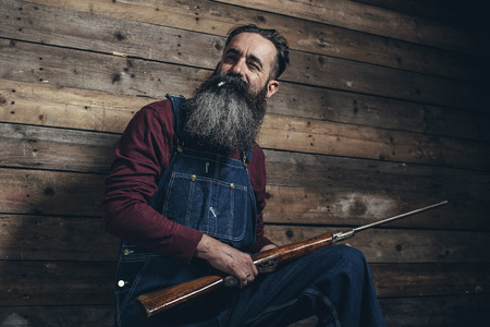 vintage rifle: Vintage farmer holding rifle standing against wooden wall in barn.