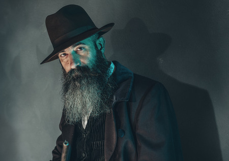 retro dark: Spooky vintage beard man with rifle in 1900 style fashion against grey wall.