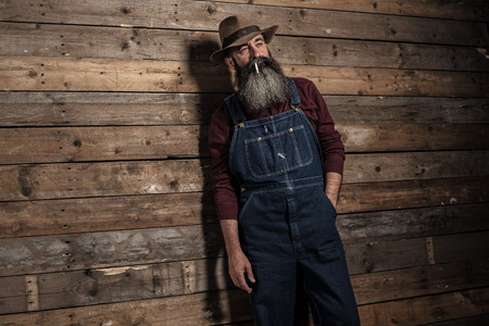 gray beard: Smoking vintage worker man with long gray beard in jeans dungarees. Standing against wooden wall.