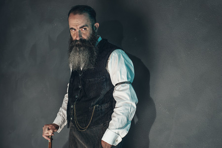 white beard: Vintage beard man in 1900 style fashion with cane against grey wall.
