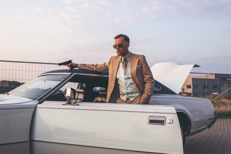 man standing alone: Retro 1970s gangster with pistol leaning against vintage car.