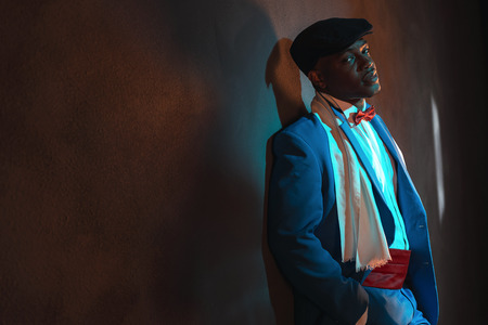 african american vintage: Retro african american man in blue suit wearing blue cap. Leaning against gray wall.