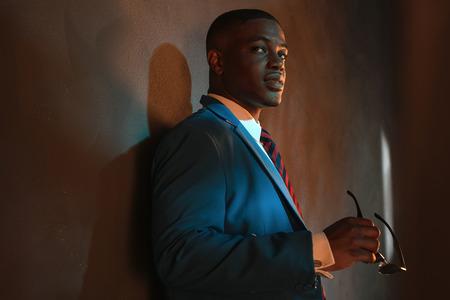 mannequin africain: Rétro africaine homme d'affaires américain en costume tenant des lunettes de soleil bleu. Appuyé contre le mur gris. Banque d'images