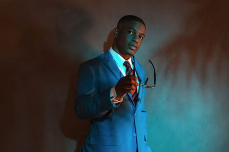 Retro african american businessman in blue suit holding sunglasses. Leaning against gray wall.