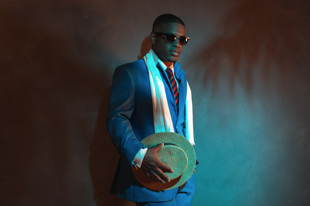 Retro african american man in blue suit wearing sunglasses. Leaning against gray wall. Stockfoto