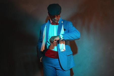 negras africanas: En busca hombre reloj retro afroamericano en traje azul que desgasta el casquillo azul.