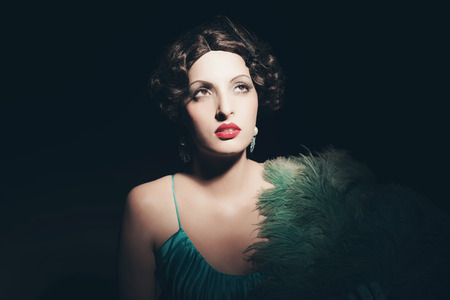 Glamour retro 1920s young woman holding a fan. Against black background. Stock Photo