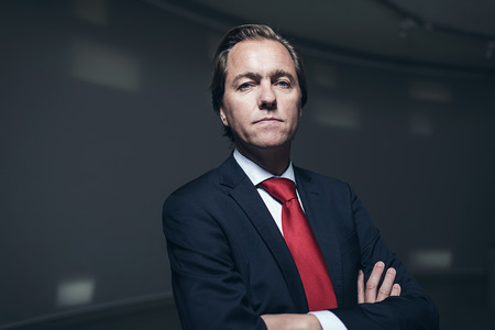 Serious confident businessman with red tie in room. Looking in camera.