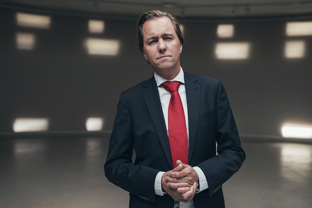 entrepreneur: Concerned entrepreneur wearing suit with red tie standing in empty room.