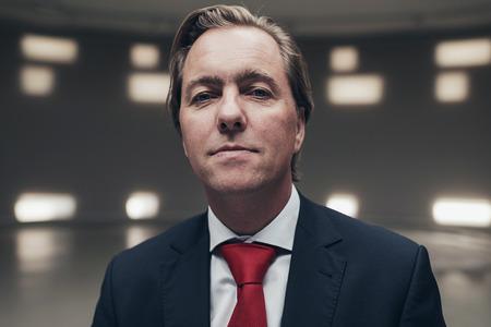 Arrogante empresario vistiendo traje con corbata roja en la habitación vacía.