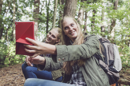 twin sister: Twin sister making selfie in forest.