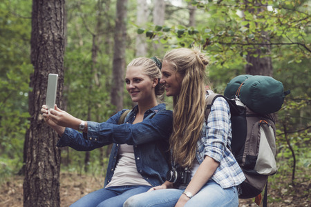 twin sister: Happy hiking twin sister in forest making selfie with tablet computer.