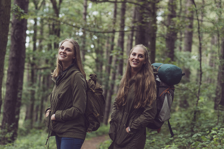 twin sister: Happy twin sister hiking in forest. Stock Photo