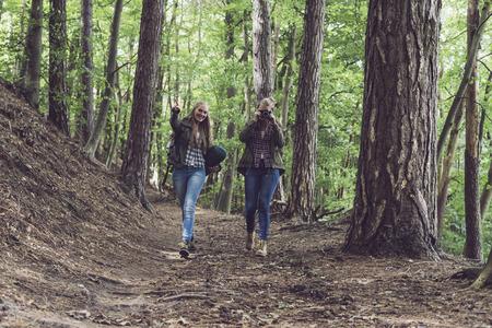 twin sister: Twin sister walking on forest trail. Walking towards camera.