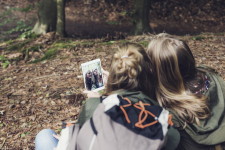 over the shoulder: Twin sister making selfie in forest. Over shoulder shot.