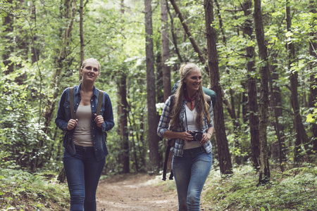 twin sister: Happy twin sister walking on forest trail with backpack. Stock Photo