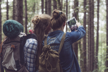 backpacking: Two backpacking friends making selfie in forest.