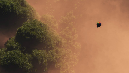 mist: High angle view of hot air balloon floating above forest in morning mist. Stock Photo