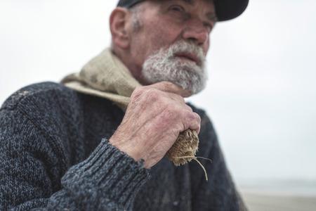 beachcombing: Hand of beachcomber holding burlap sack. Face out of focus.