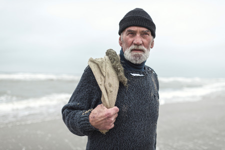 beachcombing: Senior beachcomber with burlap sack and woolen cap near sea. Stock Photo