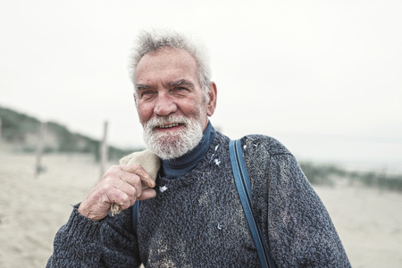 beachcombing: Smiling senior beachcomber on the beach. Holding burlap sack over shoulder.
