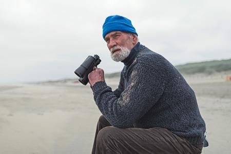 beachcombing: Beachcomber sitting on the beach holding binocular. Stock Photo