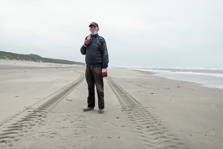 beachcombing: Portrait of senior beachcomber on the beach. Standing between car tracks.