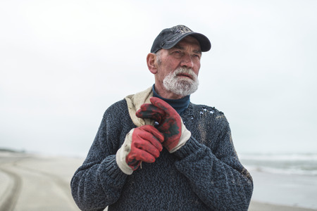 work gloves: Senior beachcomber with work gloves on the beach holding burlap sack. Staring into distance. Stock Photo