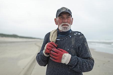 beachcombing: Senior beachcomber with work gloves on the beach holding burlap sack. Staring into distance. Stock Photo