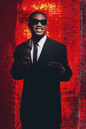 latin american: Retro 1950s male latin american singer with sunglasses in black suit and tie. Red reflections background. Stock Photo